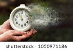 Small photo of The concept of leaving time. Old hours, in old hands. Old alarm clock. Vintage clock as time passing and pass away concept