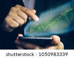 smartphone with stock market... | Shutterstock . vector #1050983339