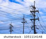 many electric poles and power... | Shutterstock . vector #1051114148