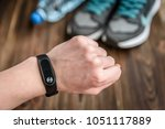 fitness tracker and sneakers on ... | Shutterstock . vector #1051117889