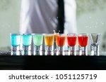 bartender pours alcoholic drink ... | Shutterstock . vector #1051125719