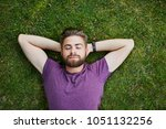 young man lying on ground in...   Shutterstock . vector #1051132256