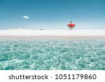 man on lilo in the sea water.... | Shutterstock . vector #1051179860