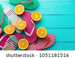 Summer fun time and flip flops. Slippers and orange fruit on blue wooden background. Mock up and picturesque. Top view. Copy space