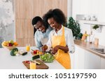 smiling woman mixing salad in... | Shutterstock . vector #1051197590