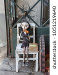 Small photo of Oporto, Portugal - july 2016: Wooden Worn-out Woman Marionette on White Chair.
