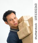 young man carrying a box  of...   Shutterstock . vector #1051332263