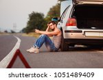 a young man sits on the asphalt ... | Shutterstock . vector #1051489409