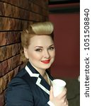 Small photo of Portrait of young blond lady with craft cup. Pin-up styled girl on brick wall background. Happy smiled woman with blonde curves