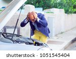 Small photo of Stressed man having trouble with his broken car looking in frustration at failed engine; hands on head looking inside to the open capote top of the car. Negativehuman emotion reaction body language