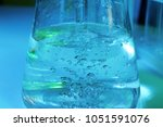 test flask with water on color... | Shutterstock . vector #1051591076