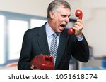angry businessman shouting on... | Shutterstock . vector #1051618574