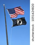 Small photo of Willard, Missouri - February 21, 2016: The American Flag with the POW MIA Flag flying against a blue sky.