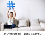 smiling woman holding a hashtag ... | Shutterstock . vector #1051733960