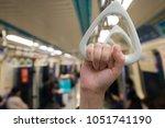 woman hand holding onto a...   Shutterstock . vector #1051741190