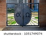 Small photo of close up of an iron gate of a cemetary with the written words alpha and omega
