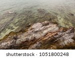 rocks in the sea evening time... | Shutterstock . vector #1051800248