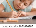 cute little girl doing homework ... | Shutterstock . vector #1051824983