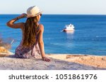 young girl sitting on the coast ... | Shutterstock . vector #1051861976