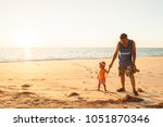Small photo of Phang Nga, Thailand - JANUARY 29, 2016: Young girl and father seeing the ocean for the first time on sunset beach of Tai Muang District.