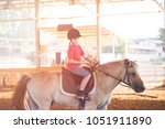 Small photo of Portrait of little boy riding a horse. First lessons of horseback riding