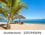 two sunbeds under a straw... | Shutterstock . vector #1051940696