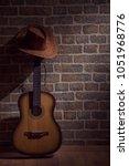 guitar har and wall  brick... | Shutterstock . vector #1051968776