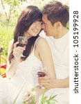 Young couple drinking wine and looking at each other - stock photo