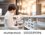 young asian man choosing... | Shutterstock . vector #1052039396