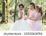 bridesmaids help bride to put... | Shutterstock . vector #1052063096