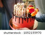 Small photo of a man holding a cake with burning candles thirty-five pieces