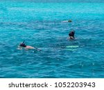 three persons snorkeling in the ... | Shutterstock . vector #1052203943
