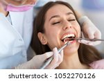dentist and patient in dentist... | Shutterstock . vector #1052270126