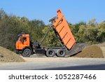the dump truck unloads rubble.... | Shutterstock . vector #1052287466