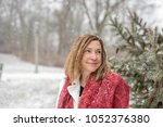 happy woman standing outside in park at Christmas with magical snow falling