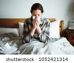 a woman suffering from flu in... | Shutterstock . vector #1052421314