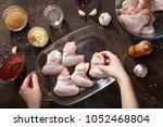 hands put chicken wings in the...   Shutterstock . vector #1052468804
