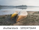Two Canoes on the Shoreline of a Lake during Sunrise in Algonquin Park, Canada.