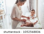 Small photo of Bright portrait of a mom changing a diaper to her baby