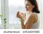 woman takes pill with omega 3... | Shutterstock . vector #1052605580