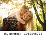 mother carrying her daughter on ... | Shutterstock . vector #1052645738