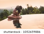 Young woman in swimsuit relaxing next to the infinity pool with jungle view during vacation retreat
