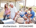 Small photo of Multi Generation Family Enjoying Cooking Barbecue At Home
