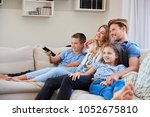 family sitting on sofa at home... | Shutterstock . vector #1052675810