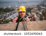 Male industry rope access wearing helmet using twin ropes, safety back up device working, abseiling, off on construction in high rise building site near the rock in Sydney city CBD, Australia    - stock photo