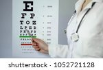 eye doctor pointing at medical... | Shutterstock . vector #1052721128