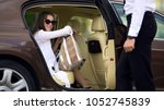 private chauffeur opening door... | Shutterstock . vector #1052745839