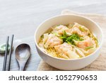 Shrimp wonton with braised pork in soup on wooden table - Asian food style, Select focus image