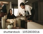 business lounge waitress... | Shutterstock . vector #1052833016