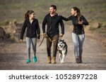 Stock photo cheerful parents with teen girl wearing sportive clothing and walking with dog on rocky road 1052897228